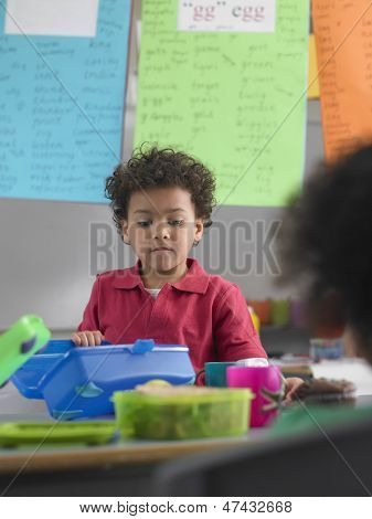 Cute young boy looking into lunchbox during break in class