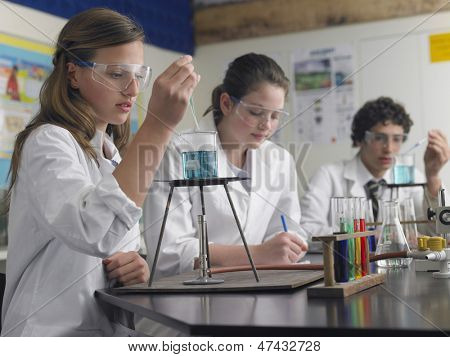 Teenage students caring out experiments in chemistry class