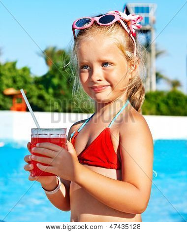 Child drinking soft drink near swimming pool.