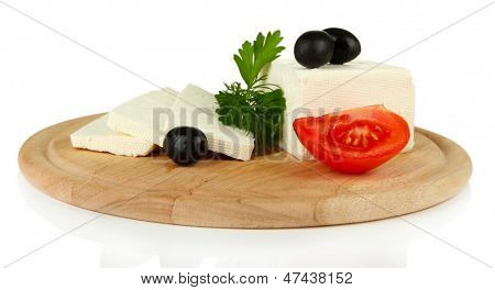 Sheep milk cheese, black olives, red tomato with parsley and dill on cutting board, isolated on white