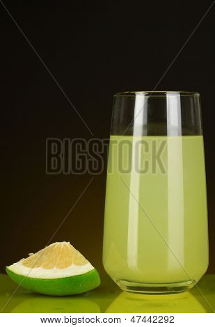 Delicious sweetie juice in glass and sweetie next to it on dark orange background