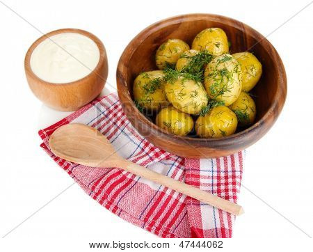 Boiled potatoes on wooden bowl on napkins isolated on white