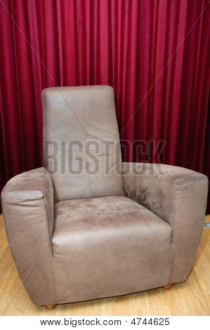 Big Brown Leather Chair Against Red Velvet Curtains