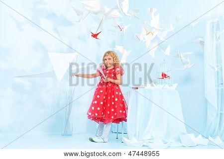 Beautiful little girl in her  dream world feeding paper birds.
