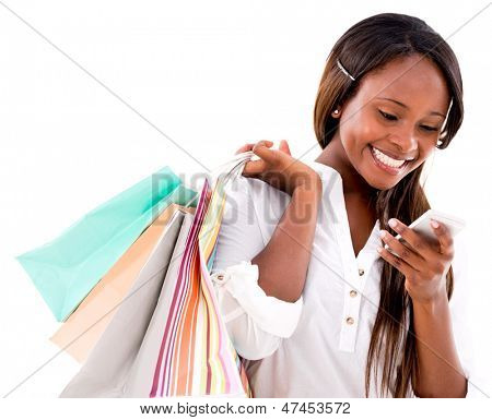 Happy shopping woman texting on her cell phone - isolated over white