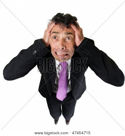 High angle full length portrait of an expressive anxious businessman tearing at his hair isolated on white