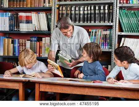Mature male teacher showing book to schoolboy with students studying at table in library
