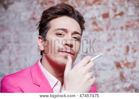 Portrait of young man in pink suit with cigarette against scuffed brick wall