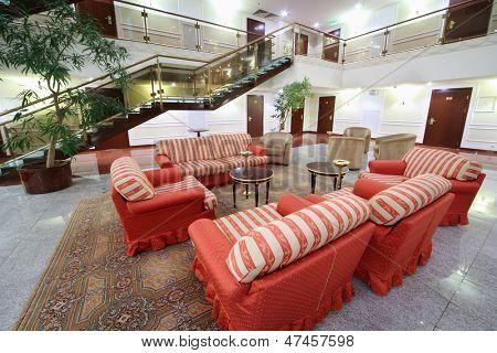 Atrium mit roten Plüschsesseln, Sofas und Treppen in stilvollen Hotel.