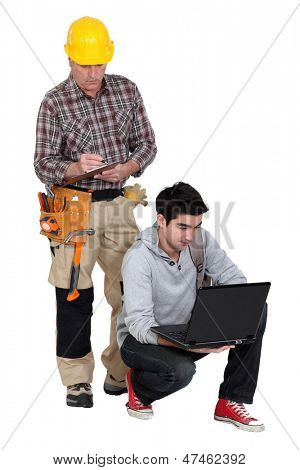Carpenter stood by young apprentice using laptop