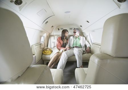 Couple sitting in private jet