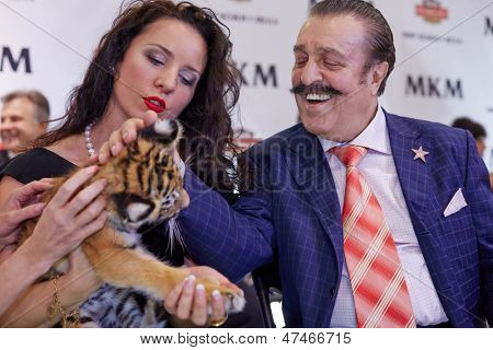 MOSCOW - OCT 22: Circus actress, tamer, animal trainer Karina Bagdasarova with tiger cub and american and russian singer Willy Tokarev at Phoney New Year celebration, October 22, 2012, Moscow, Russia.