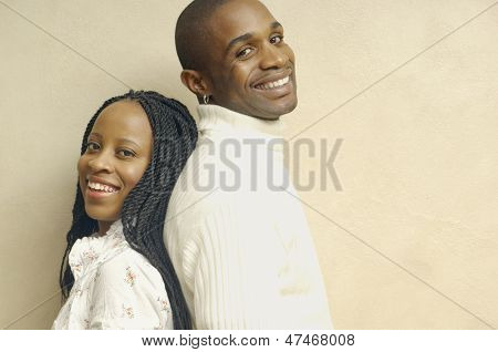 Couple standing back to back smiling