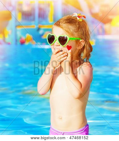 Closeup on sweet baby girl having fun in swimming pool, adorable child with red heart paint print on cheek wearing cute sunglasses, summer holidays in aquapark