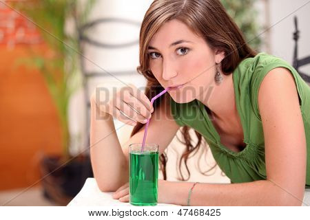 Attractive brunette drinking mint cordial