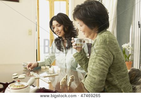 Mother and adult daughter playing dominoes