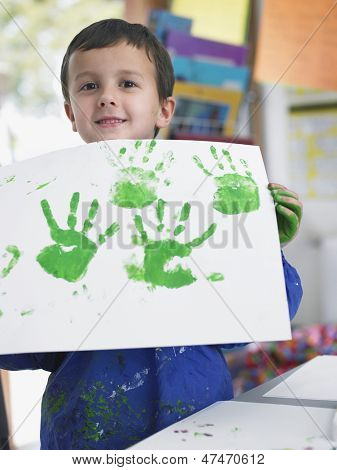 Portrait of young boy presenting his finger painting in art class