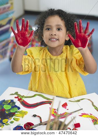 Portrait of cute little girl finger painting in art class
