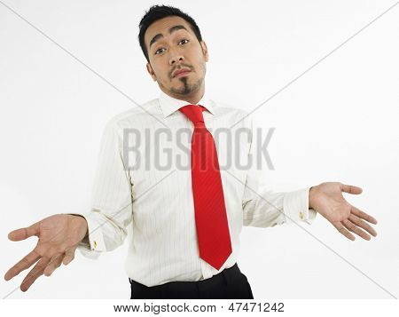 Portrait of a male executive shrugging off against white background