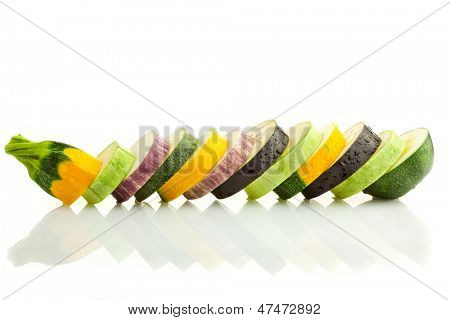 Different kind of courgettes (zucchini) and eggplants / colorful slices / horizontal border isolated on white with real reflection