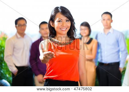 Asian Creative team - young businesspeople are successful with a project greeting a new team member