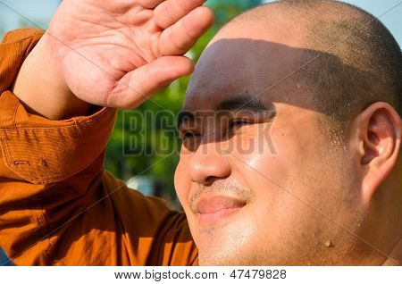 A Bald Head Man Is Protecting His Eye From Sunlight