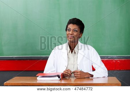 Thoughtful young African American female teacher looking away while sitting at desk in classroom