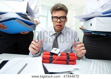 Frightened accountant with dynamite being surrounded by big heaps of papers
