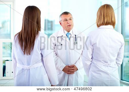 Portrait of mature doctor talking to one of two young clinicians in hospital