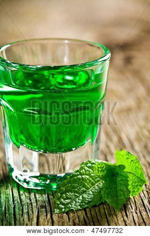 green mint liquor on wooden table