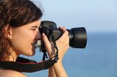 foto of megapixel  - Attractive woman taking a photograph with her camera with the sea in the background - JPG