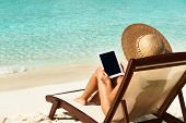 picture of beach hat  - Young woman in hat with tablet pc at the beach - JPG