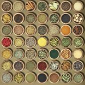 stock photo of cinnamon  - Large collection of metal bowls full of herbs and spices - JPG