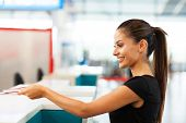 foto of over counter  - attractive businesswoman handing over air ticket at airport check in counter - JPG