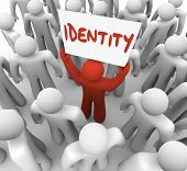 stock photo of integrity  - One person holds a sign or banner with the word Identity to spread awareness of his unique brand - JPG