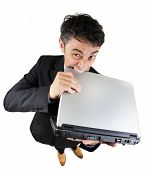 Humorous high angle full length portrait of a frustrated businessman biting his laptop computer in d