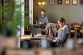 stock photo of internet-cafe  - Side view of pregnant woman using digital tablet at cafe - JPG
