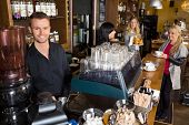 Portrait of male bartender with colleague working in background at cafe