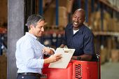 stock photo of pallet  - Fork Lift Truck Operator Talking To Manager In Warehouse - JPG