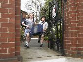 Full length of elementary students running out through school gate