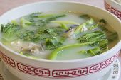 stock photo of chinese parsley  - Fish Head Soup with Chinese Vegetable Parsley Tofu and Cilantro Closeup - JPG