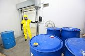 stock photo of toxic substance  - technician in protective uniform checking barrels with toxic substance in plant - JPG
