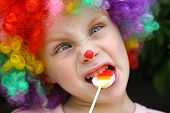 foto of clown face  - A cute little boy dressed up in a clown costume making a silly face and eating a lollipop - JPG