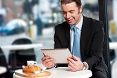 stock photo of eatables  - Corporate male manager reviewing business updates on tablet pc while waiting for his order - JPG