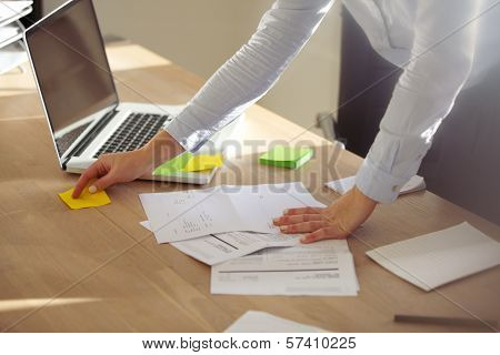 Businesswoman Checking Notes On Post It