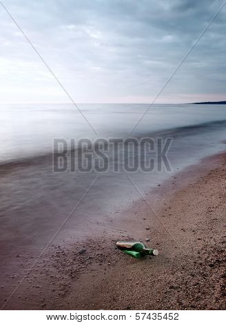Bottle With Message On Sea Coast
