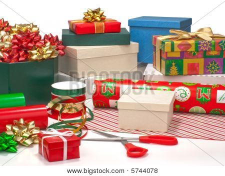 Wrapping Christmas Presents.  Gift Boxes, Wrapping Paper, Ribbons, Bows Isolated On White.