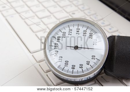 Close Up Of Sphygmomanometer On Laptop Keyboard