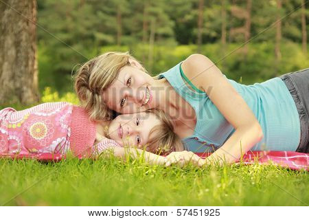 Mama And Her Little Daughter On The Grass