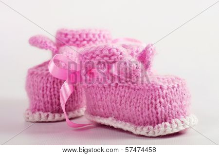 Knitted pink baby booties on the background